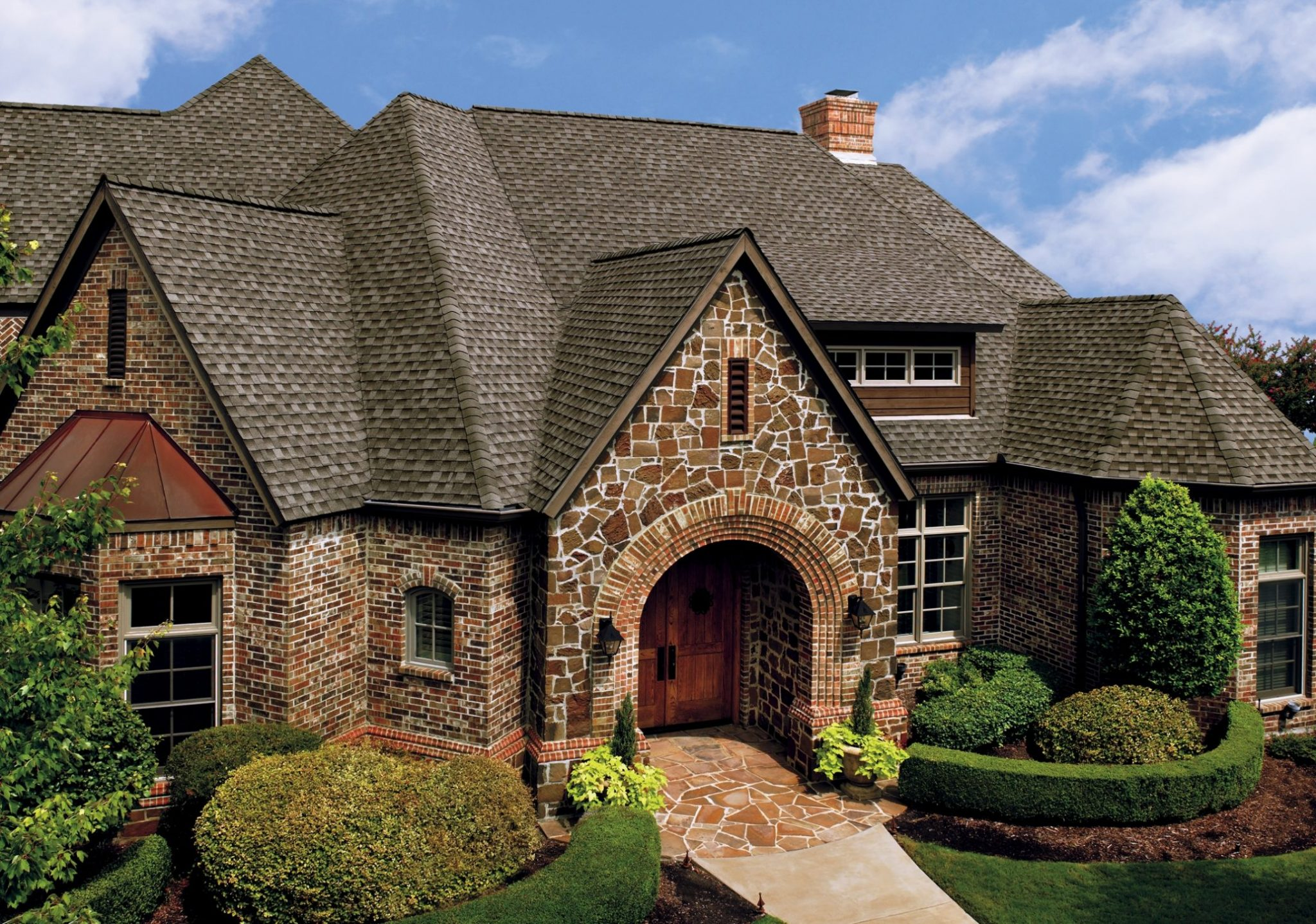 Timberline HD Asphalt Shingles in Weathered Wood colour on Large Brick Cottage Style House